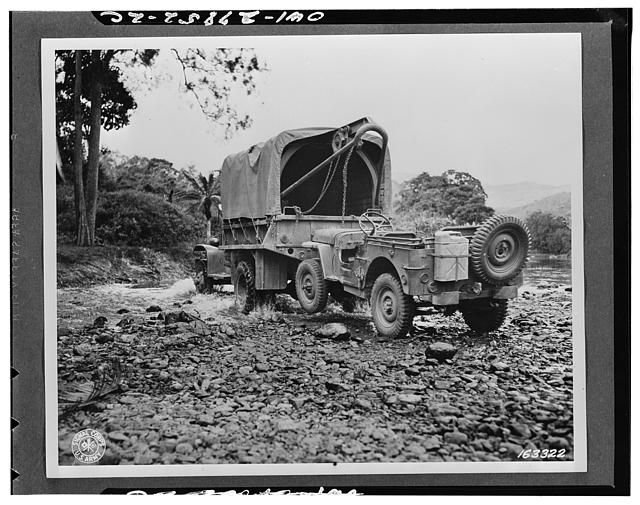 A one-and-a-half ton truck with wrecker mount pulling in a jeep during maneuvers somewhere in New Caledonia