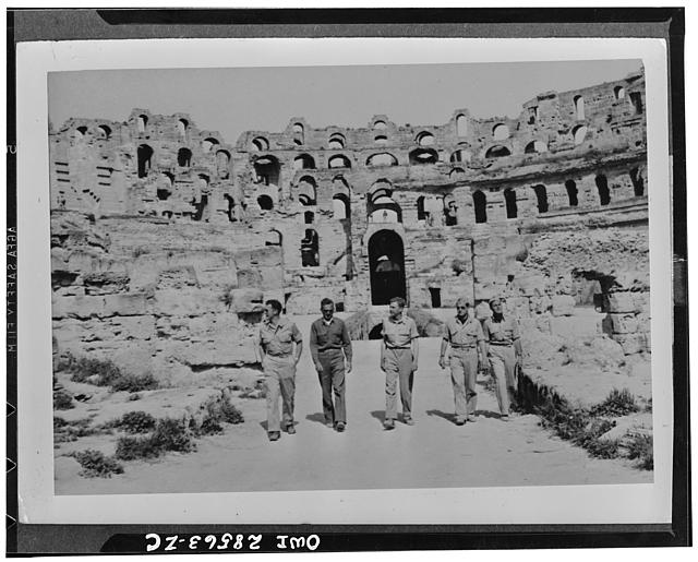 Officers of the 57th Fighter group United States Army Air Force, look over the ruins of a Roman coliseum in Tunisia. These are a few of our airmen who knocked Nazi planes out of the skies above Sicily Straits and are now getting their birdeye's of Italy, itself