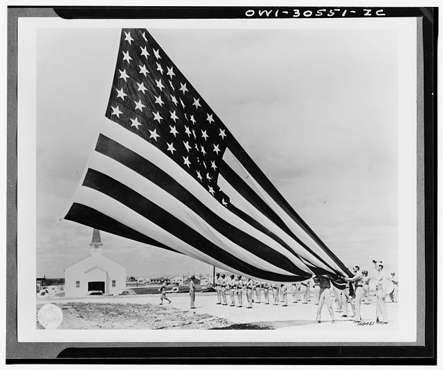 Soldier unfolding Garrison flags at Fort Hood, Texas