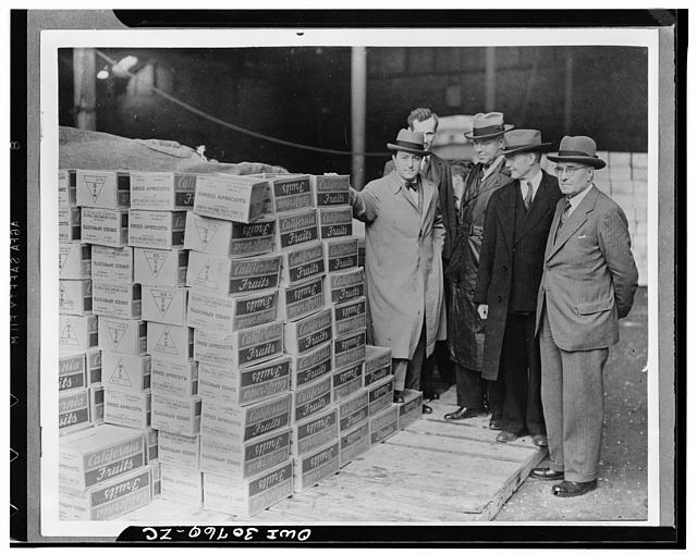 Mr. Lloyd Steer, and Mr. Paul Appleby, U.S. Undersecretary of Agriculture, and Mr. Rudolph Evans, U.S. Administrator of Agricultural Adjustment Administration, examining boxes of dried apricots on the quayside at a British port