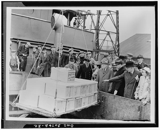 Meeting first American food ship to arrive under lend-lease to Britain. Right to Left: Kathleen Harriman, Lord Woolton, Minister of Food; Averill Harriman, U.S. lend lease representative; Robert H. Hinkley, U.S. Assistant Secretary of Commerce, watching a consignment of food being lifted from the hold of the ship at a British port
