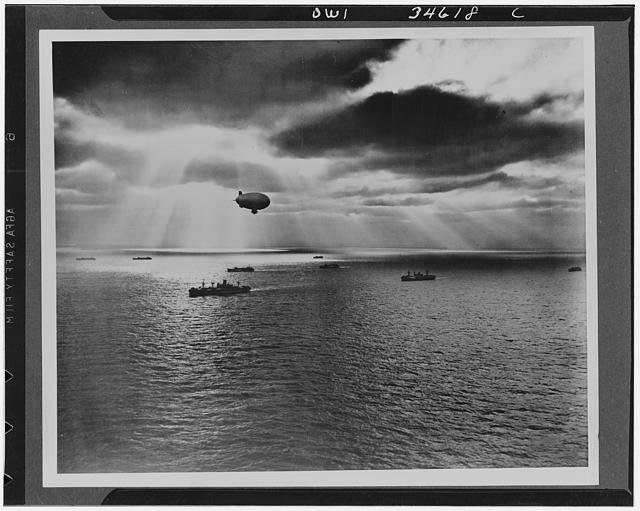Sunset over the Atlantic finds another United Nations convoy moving peacefully towards it destiniation. A U.S. Navy blimp, hovering watchfully overhead, is on the lookout for any sign of enemy submarines