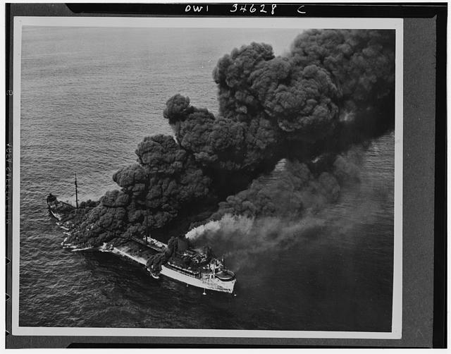 A U.S. tanker torperdoed by an Axis submarine. Despite a raging fire which sent columns of black oily smoke billowing into the sky, crew members were able to bring the flames under control, and the tanker was towed to port by a U.S. naval ship