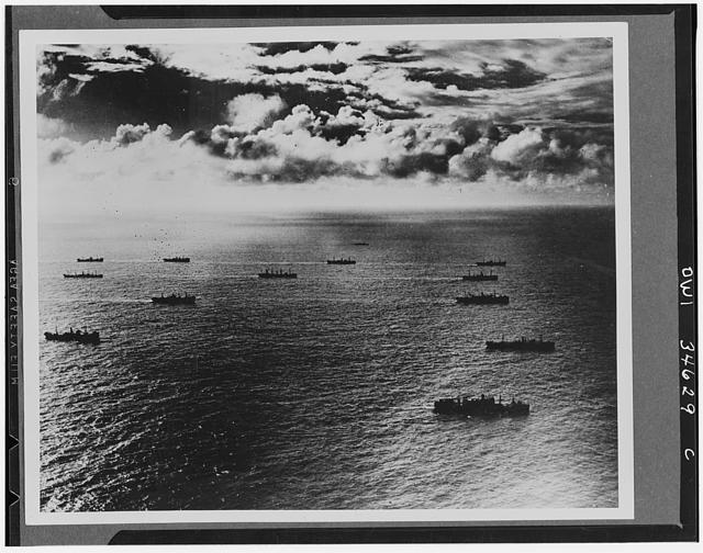 Sturdy cargo ships fill the sea lanes leading to all fronts, bearing guns, tanks, and planes for the United Nations. The Liberty ships are visible in this section of the convoy