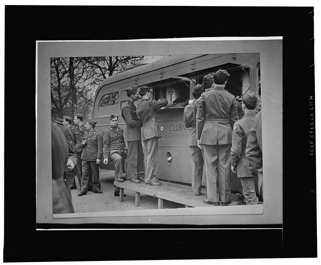 "London, England. United States soldiers receiving refreshments, including doughnuts, from an American Red Cross clubmobile at the end of the Allied nations' parade in a ""Wing for Victory"" week celebration"