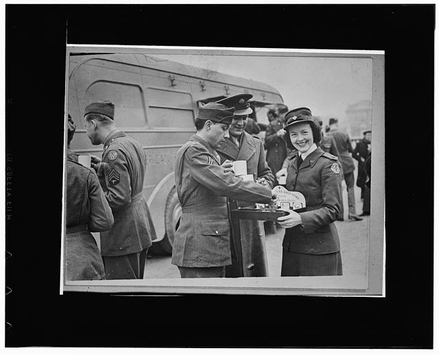"London England. Hope Simpson, from Montreal, offering American soldiers cigarettes and candy after they have taken part in the Allied nations' procession, a feature of London's ""Wings for Victory"" week celebration. Miss Simpson has been living in London for six years, but was in France when that nation fell to the Nazis. She is now serving with the American Red Cross."