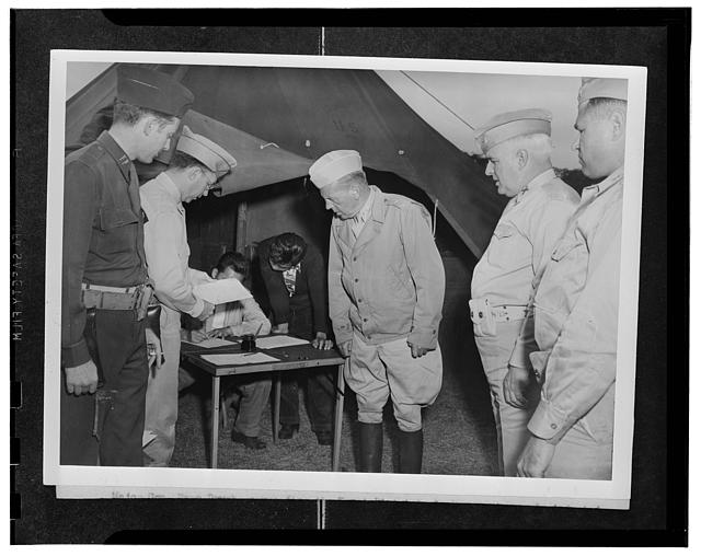 Kauai District, Territory of Hawaii. A newly-inducted AJA volunteer receiving a pass to return home to settle his personal affairs. Major General Rapp Brush and Colonel J.J. Doyle are looking on