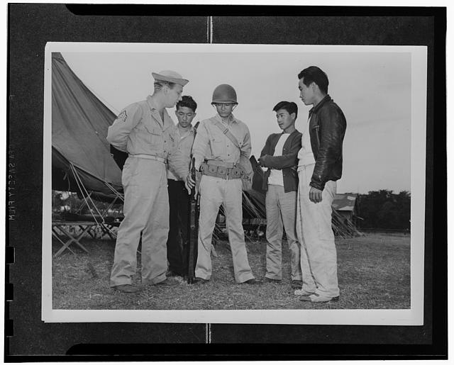 Kauai District, Territory of Hawaii. Sergeant John H. Chynoweth showing Mitsuru Doi, first AJA volunteer how to hold his rifle when at ease