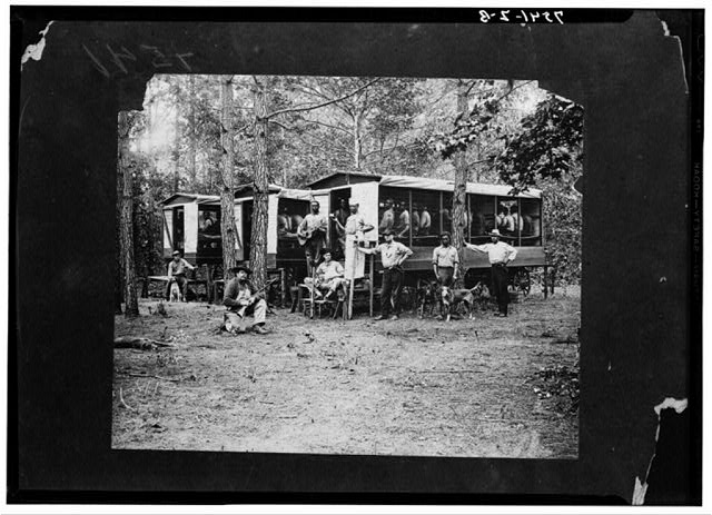 Chain gang of convicts engaged in road work. Pitt County, North Carolina. Autumn 1910. The inmates were quartered in the wagons shown in the picture. Wagons were equipped with bunks and move from place to place as labor is utilized. The central figure in the picture is J.Z. McLawhon, who was at that time county superintendent of chain gangs. The dogs are bloodhounds used for running down any attempted escapes