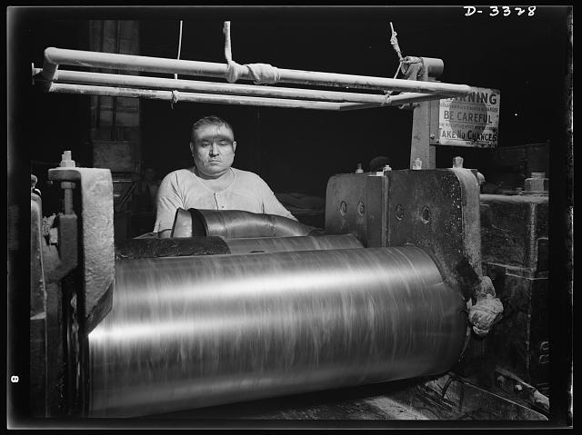 "Rubber stock for the track treads of scout cars and other Army halftrac vehicles is milled in one Ohio tire plant. All rubber firmly ""welded"" to the steel parts is formed into one tough durable piece. Goodrich, Akron, Ohio"