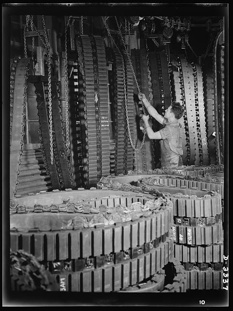 A huge and rapidly increasing supply of tracks for Army halftrac cars comes from one Ohio tire plant alone. Traveling chain hoists carry tracks from the curing press to trimming racks on which curing plates and overflowing edges of rubber are removed. Goodrich, Akron, Ohio