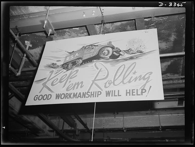 The halftrac production department of an Ohio tire plant now handling a large Army order displays a poster that expresses the sentiments of the management and the workers. Goodrich, Akron, Ohio
