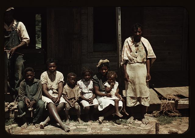 Bayou Bourbeau plantation, a FSA cooperative, Natchitoches, La. A Negro family (?) seated on the porch of a house