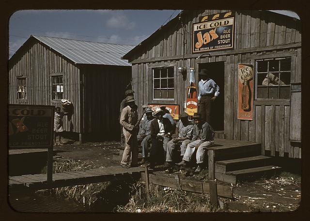 "Migratory laborers outside of a ""juke joint"" during a slack season, Belle Glade, Fla."