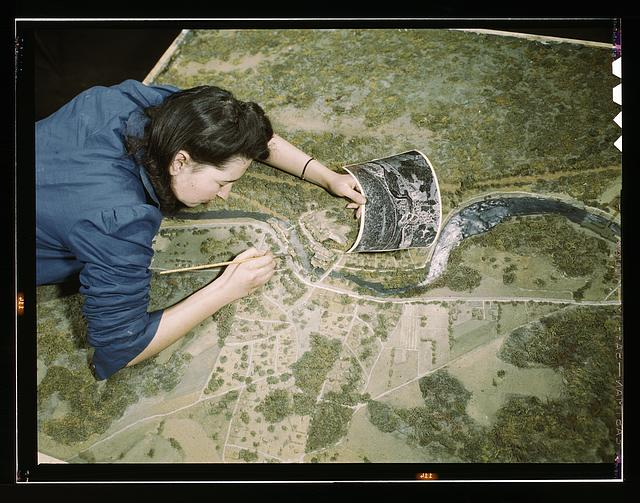 Camouflage class at N[ew] Y[ork] University, where men and women are preparing for jobs in the Army or in industry, New York, N.Y. This model has been camouflaged and photographed. The girl is correcting oversights detected in the camouflaging of a model defense plant