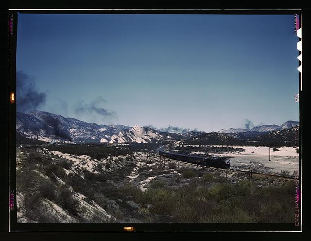 "Santa Fe R.R. trains going through Cajon Pass in the San Bernardino Mountains, Cajon, Calif. On the right, streamliner ""Chief"" going west; in the background, on the left, a freight train with a helper engine, going east. Santa Fe trip"