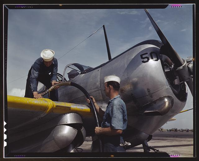 Feeding an SNC advanced training plane its essential supply of gasoline is done by sailor mechanics at the Naval Air Base, Corpus Christi, Texas. Standing on the wing is Floyd Helphrey who came from Iowa to join the Navy early in the year. At right is W. Gardner of Illinois who used to be a crane operator