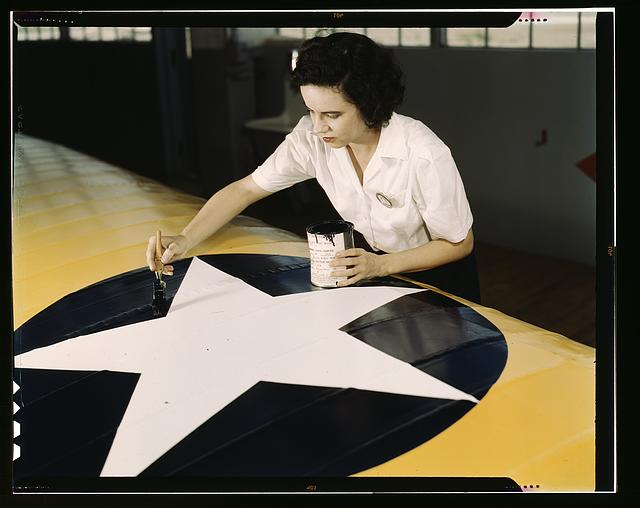 Women from all fields have joined the production army, Corpus Christi, Texas. Miss Grace Weaver, a civil service worker at the Naval Air Base, and a school teacher before the war, is doing her part for victory along with her brother who is a flying instructor in the Army. Miss Weaver paints the American insignia on repaired Navy plane wings