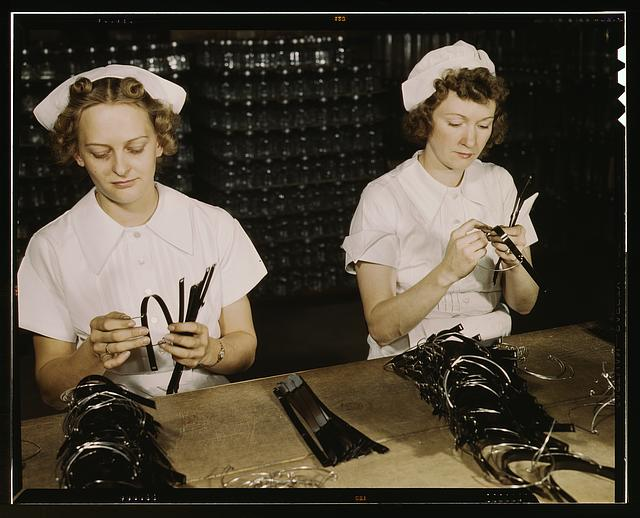 Two Navy wives, Eva Herzberg and Elve Burnham, entered war work after their husbands joined the service, Glenview, Ill. They assemble bands for blood transfusion bottles at Baxter Laboratories. Mrs. Burnham is the mother of two children