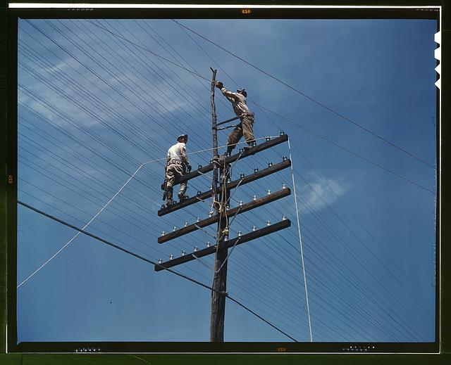 [Men working on telephone lines, probably near a TVA dam hydroelectric plant]