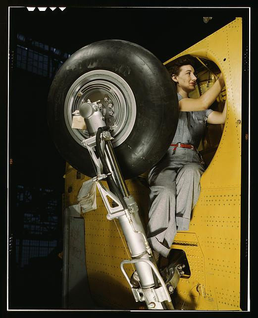 "This woman worker at the Vultee-Nashville is shown making final adjustments in the wheel well of an inner wing before the installation of the landing gear, Nashville, Tenn. This [is] one of the numerous assembly operations in connection with the mass production of Vultee ""Vengeance"" dive bombers"
