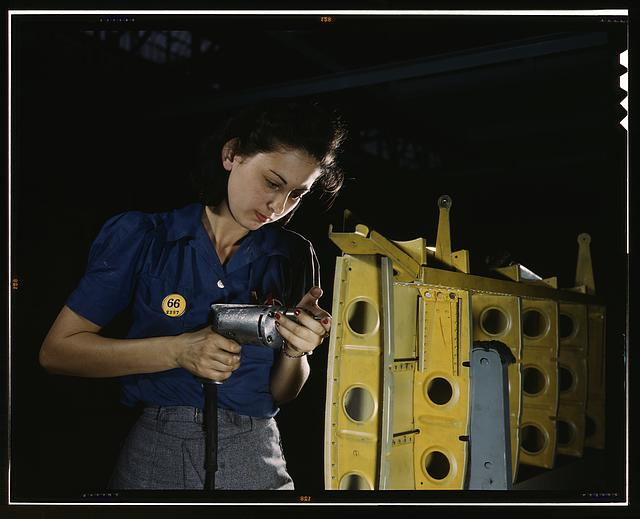 "Drilling horizontal stabilizers: operating a hand drill, this woman worker at Vultee-Nashville is shown working on the horizontal stabilizer for a Vultee ""Vengeance"" dive bomber, Tennessee. The ""Vengeance"" (A-31) was originally designed for the French. It was later adopted by the R.A.F. and still later by the U.S. Army Air Forces. It is a single-engine, low-wing plane, carrying a crew of two men and having six machine guns of varying calibers"