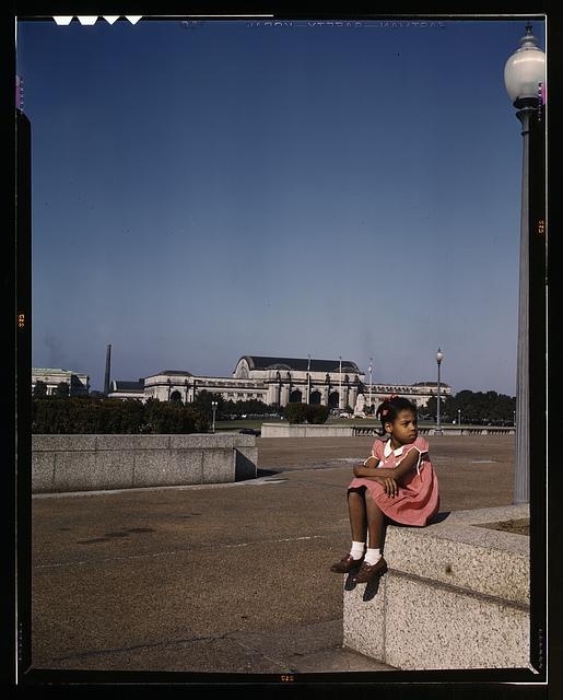 Little girl in a park with Union Station in the background, Washington, D.C.