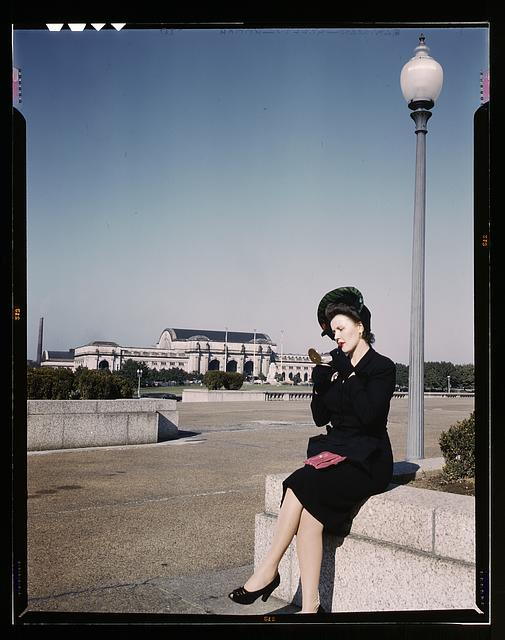 Woman putting on her lipstick in a park with Union Station behind her, Washington, D.C.
