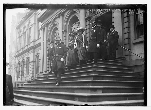Suffragettes, preceded by policemen, decend steps of City Hall, New York