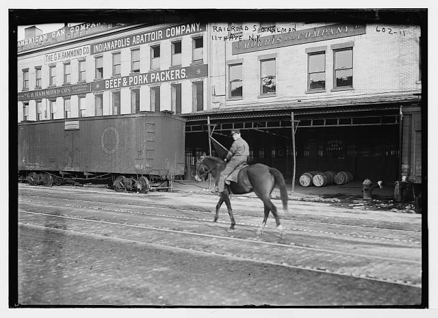 Railroad cars and equestrian signalman on 11th Ave., New York