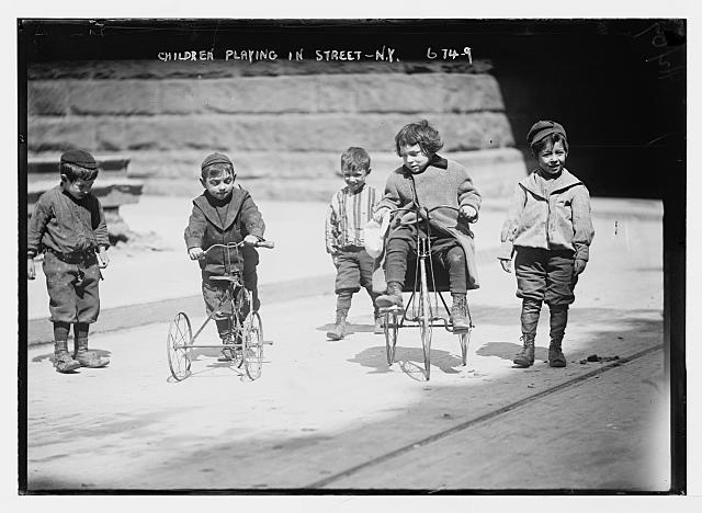 Children with tricycles, playing in street, New York