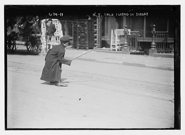 Children with stick playing in street, New York