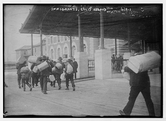 Immigrants carrying luggage, Ellis Island, New York