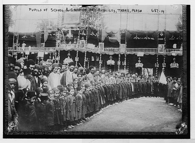 Pupils of school & group of anti-royalists, Tabriz, Persia [Large group of uniformed children with adults in rear; large balconied building with striped columns in background]