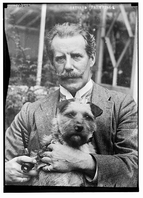 Bernard M. Partridge holding dog