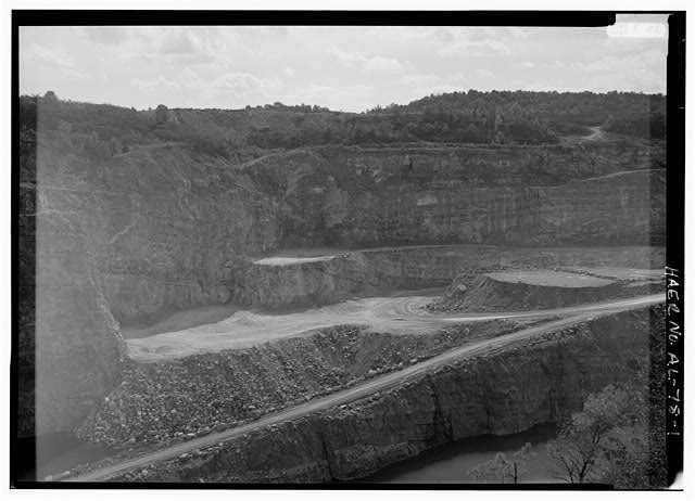 EXTERIOR OVERVIEW, LOOKING NORTH, OF THIS 400' DEEP LIMESTONE QUARRY PIT ('THE OLD PIT') WITH LEDGE PREPARED FOR LIMESTONE EXTRACTION. AN ELEVEN-HOLE SHOT WILL DISLODGE APPROXIMATELY 25,000 TONS OF LIMESTONE WHICH, AFTER LOADING AND CRUSHING, WILL BE USED FOR ROAD CONSTRUCTION. THE CALERA QUARRY IS ONE OF FOUR ACTIVE VULCAN MATERIALS COMPANY QUARRIES IN THE DISTRICT. VULCAN MATERIALS, A FORTUNE 500 FIRM, ESTABLISHED IN BIRMINGHAM IN 1906 AS BIRMINGHAM SLAG COMPANY, VULCAN MATERIALS IS THE NATION'S FOREMOST PRODUCER OF CONSTRUCTION AGGREGATE AND A LEADING CHEMICALS MANUFACTURER. - Vulcan Material Company, Calera Quarry, 1614 Highway 84, Calera, Shelby County, AL