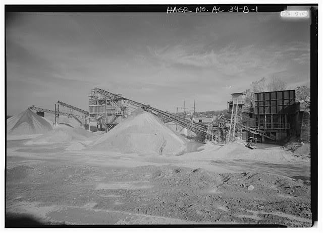 EXTERIOR VIEW, LOOKING EAST, OF REDUCTION PLANT NO. 6 WITH PRIMARY AND SECONDARY LIMESTONE REDUCTION ('CRUSHING') IN PROGRESS. FEEDER (RIGHT) FEEDS TO CONVEYOR BELTS (CENTER) AND CRUSHER (LEFT). LIMESTONE PROCESSED THROUGH THIS OPERATION IS FURTHER SCREENED AND PROCESSED AT ANOTHER PLANT ON THE THOMAS SITE. OPERATION OF THIS PLANT, WHICH BEGAN IN 1960, INCORPORATES WITHIN THE FEEDER A CONCRETE RETAINING WALL DATING TO A TURN OF THE CENTURY QUARRY OPERATION FORMERLY ON THIS SITE. - Wade Sand & Gravel Company, Reduction Plant No. 6, State Route 78, Thomas, Jefferson County, AL