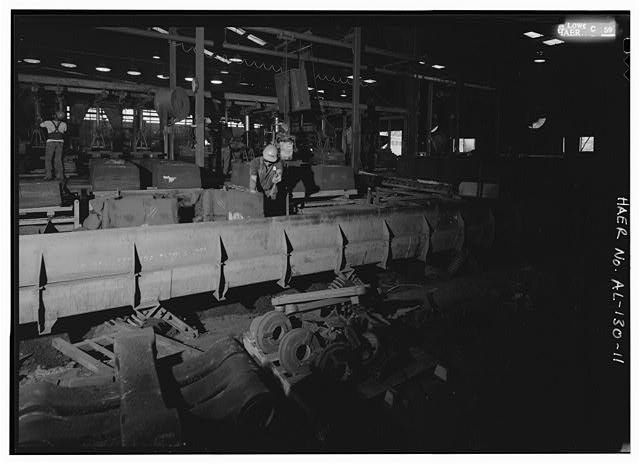SHAKE OUT WORKER DUMPING COOLED MOLDS ONTO THE VIBRATING CONVEYOR THAT TRANSPORTS SAND AND CASTINGS TO THE SEPARATION SCREEN. - Southern Ductile Casting Company, Centerville Foundry, 101 Airport Road, Centreville, Bibb County, AL