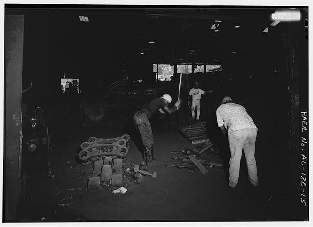 WORKERS MANUALLY 'DEGATING' OR REMOVING SPRUES AND RUNNERS FROM CASTINGS WITH SLEDGE HAMMERS. - Southern Ductile Casting Company, Centerville Foundry, 101 Airport Road, Centreville, Bibb County, AL