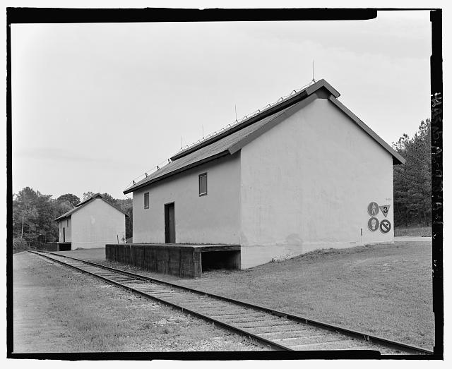 Oblique view of rear and south sides of ammunition storage buildings 4404 and 4405, view towards the north with scale - Fort McClellan Ammunition Storage Area, Building No. 4404, Second Avenue (Magazine Road), Anniston, Calhoun County, AL