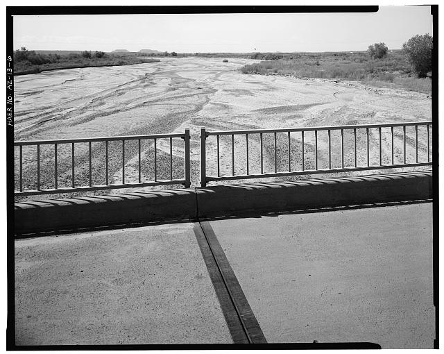 6.  DETAIL OF STEEL GUARDRAIL, CONCRETE CURB AND DECK EXPANSION JOINT, WITH DRY BED OF RIO PUERCO IN BACKGROUND. VIEW TO EAST. - Rio Puerco Bridge, Mainline Road, spanning Rio Puerco, Holbrook, Navajo County, AZ