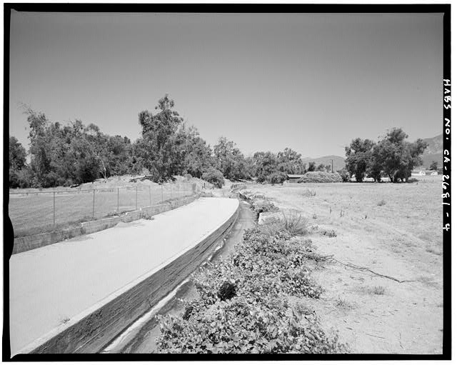 "Contextual view showing drainage culvert in foreground boarding east side of knoll with eucalyptus windbreak.  Camera facing 278"" southwest. - Goerlitz House, 9893 Highland Avenue, Rancho Cucamonga, San Bernardino County, CA"