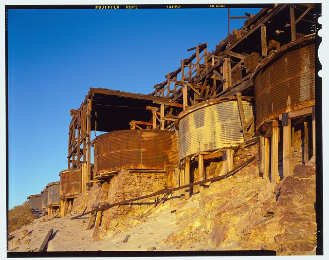 50.  OBLIQUE VIEW OF CYANIDE TANKS, LOOKING EAST SOUTHEAST, SHOWING TANK SUPPORTS AND MASONRY FOUNDATIONS. THE SUPPORTING TIMBERS WERE ADDED DURING THE MILL STABILIZATION EFFORT IN THE 1990'S. THE TANKS ARE HANGING OVER THE FOUNDATIONS TO GIVE ACCESS TO THE TRAP DOOR IN THEIR BOTTOMS FOR EMPTYING THE SANDS AFTER PROCESSING (SEE CA-290-37). SEE CA-290-36 FOR IDENTICAL B&W NEGATIVE. - Skidoo Mine, Park Route 38 (Skidoo Road), Death Valley Junction, Inyo County, CA