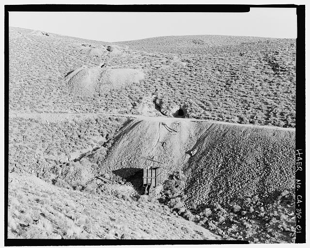 1.  VIEW OF ORE BIN ADITS, AND OVERBURDEN, LOOKING SOUTHEAST, LOCATED APPROXIMATELY 200m EAST OF MILL SITE MAIN ACCESS ROAD FROM SKIDOO TOWN SITE TO THE MILL RUNS ACROSS CENTER. TRAVELING ON THE ROAD FROM LEFT TO RIGHT GOES TOWARD THE MILL FROM THE TOWN. SEE CA-290-39 (CT) FOR IDENTICAL COLOR TRANSPARENCY. - Skidoo Mine, Park Route 38 (Skidoo Road), Death Valley Junction, Inyo County, CA