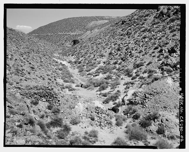2.  VIEW OF EAST TAILING DAM (FOREGROUND), LOOKING EAST SOUTHEAST UP WASH TOWARD ORE BIN, OVERBURDEN, ADITS, AND ROAD SHOWN IN CA-290-1. MILL SITE IS UP AND TO THE RIGHT OF THIS VIEW. STANDARD FIFTY-GALLON DRUM IN FOREGROUND GIVES SCALE OF WALL. - Skidoo Mine, Park Route 38 (Skidoo Road), Death Valley Junction, Inyo County, CA