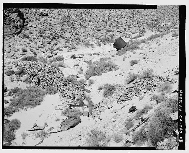 3.  VIEW OF WEST TAILING DAM, LARGE TANK, AND TAILING, LOOKING NORTHEAST. A SIX-FOOT SCALE IS LOCATED AGAINST WALL ON LEFT. PURPOSE OF TANK IS UNKNOWN, BUT APPEARS TO HAVE FALLEN FROM ITS ORIGINAL LOCATION AT THE MILL SITE, UP AND TO THE RIGHT OF THIS VIEW. - Skidoo Mine, Park Route 38 (Skidoo Road), Death Valley Junction, Inyo County, CA