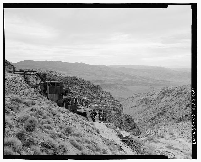 7.  OBLIQUE OVERVIEW OF NORTHEAST SIDE OF SKIDOO MILL, LOOKING WEST FROM ACCESS ROAD. DEAT VALLEY IS BETWEEN THE CLOSEST AND FARTHEST MOUNTAINS. - Skidoo Mine, Park Route 38 (Skidoo Road), Death Valley Junction, Inyo County, CA