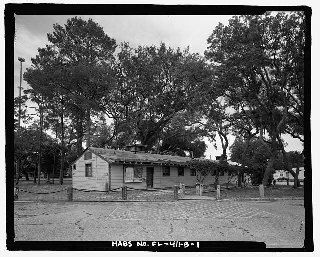 OBLIQUE VIEW OF WEST (FRONT) AND NORTH FACADES, LOOKING SOUTHEAST - Eglin Air Force Base, Storehouse & Company Administration, Southeast of Flager Road, Nassau Lane, & southern edge of Weekly Bayou, Valparaiso, Okaloosa County, FL