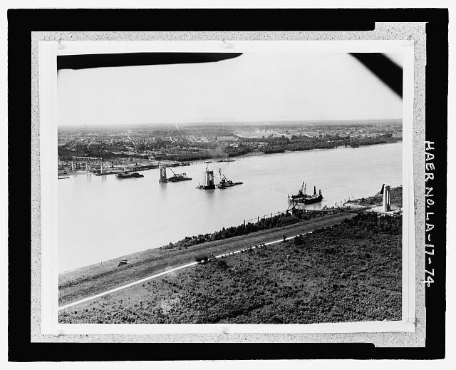 """Photographic copy of circa 1934, 10"""" x 15"""", black and white aerial photograph.  Loose in oversized box located at the National Museum of American History, Smithsonian Institution, Archives Center, Work and Industry Division, Washington, D.C.  Original Photographer unknown. AERIAL PHOTOGRAPH OF BRIDGE UNDER CONSTRUCTION FROM WEST BANK LOOKING NORTH TOWARD EAST BANK DOWN RIVER SHOWING OVERALL VIEW OF BRIDGE PIER CONSTRUCTION. - Huey P. Long Bridge, Spanning Mississippi River approximately midway between nine & twelve mile points upstream from & west of New Orleans, Jefferson, Jefferson Parish, LA"""