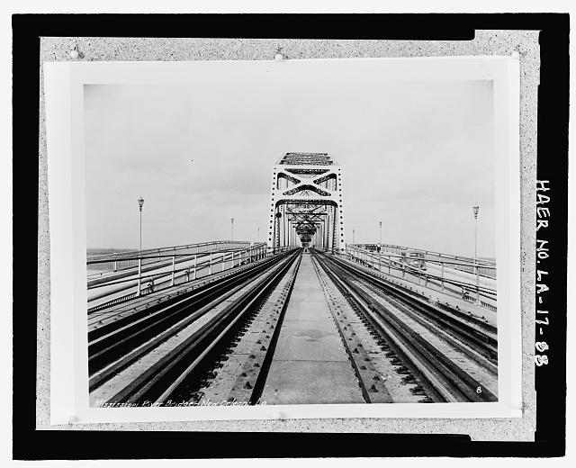 "Photographic copy of circa 1935, black and white, 10"" x 14"" photograph.  Located in box 14 of Huey P. Long Bridge folder (Greater New Orleans),  at the National Museum of American History, Smithsonian Institution, Archives Center, Work and Industry Division, Washington, D.C.   Original Photographer unknown. PHOTOGRAPH OF COMPLETED BRIDGE TAKEN IN CENTER LOOKING SOUTHEAST AT EAST BANK SINGLE THROUGH TRUSS SPAN SHOWING PERIOD AUTOMOBILE AND WOMAN ON BICYCLE WEST BOUND. - Huey P. Long Bridge, Spanning Mississippi River approximately midway between nine & twelve mile points upstream from & west of New Orleans, Jefferson, Jefferson Parish, LA"